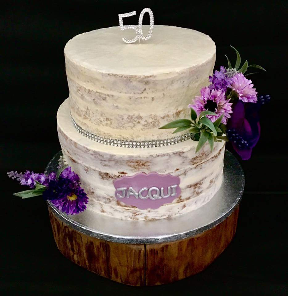Barely iced white 50th birthday cake with purple flowers