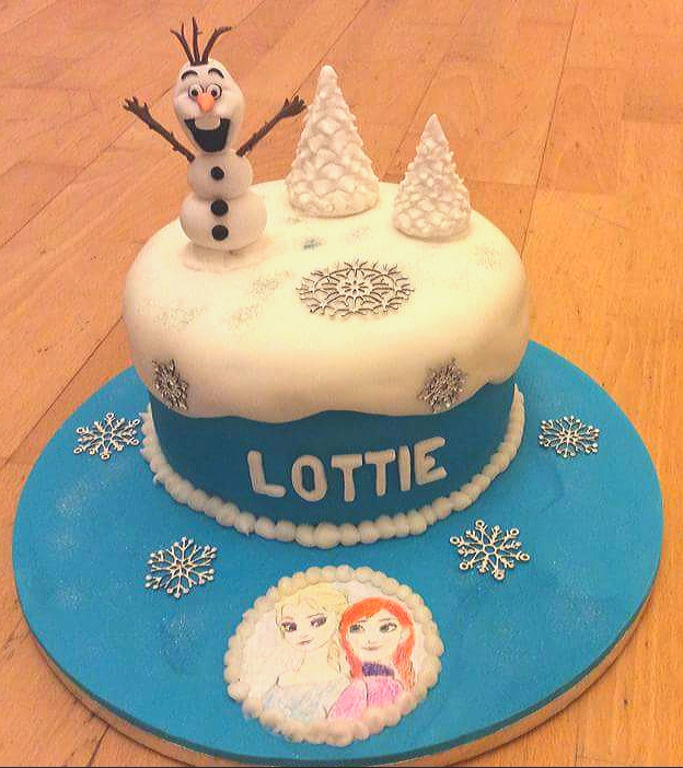 Frozen movie themed birthday cake with Olaf the snowman sitting on top