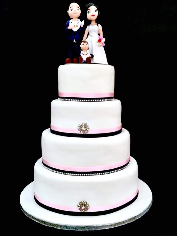 4 tier wedding cake with white icing, pink and black ribbon detail and moulded family cake topper