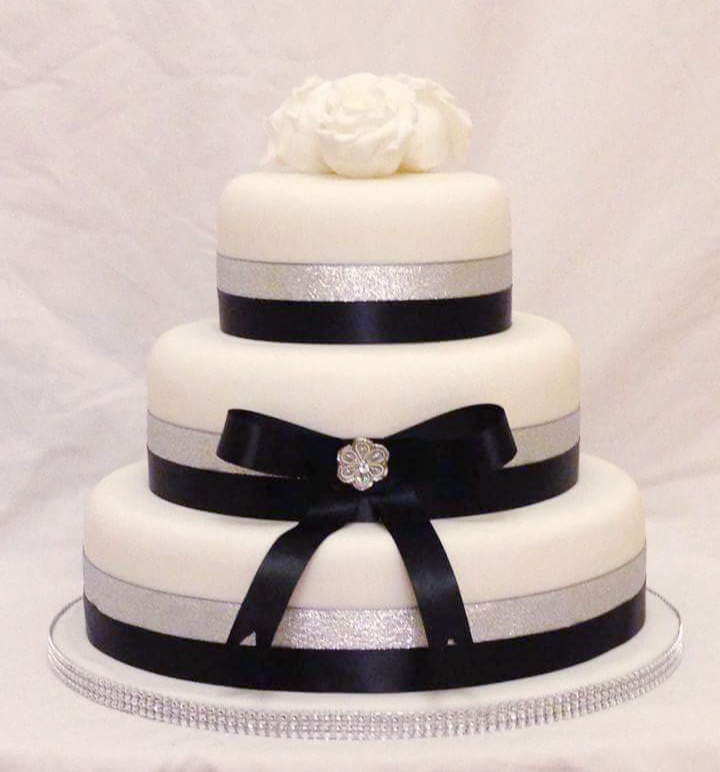 3 tier wedding cake with white icing and silver and black bow detail