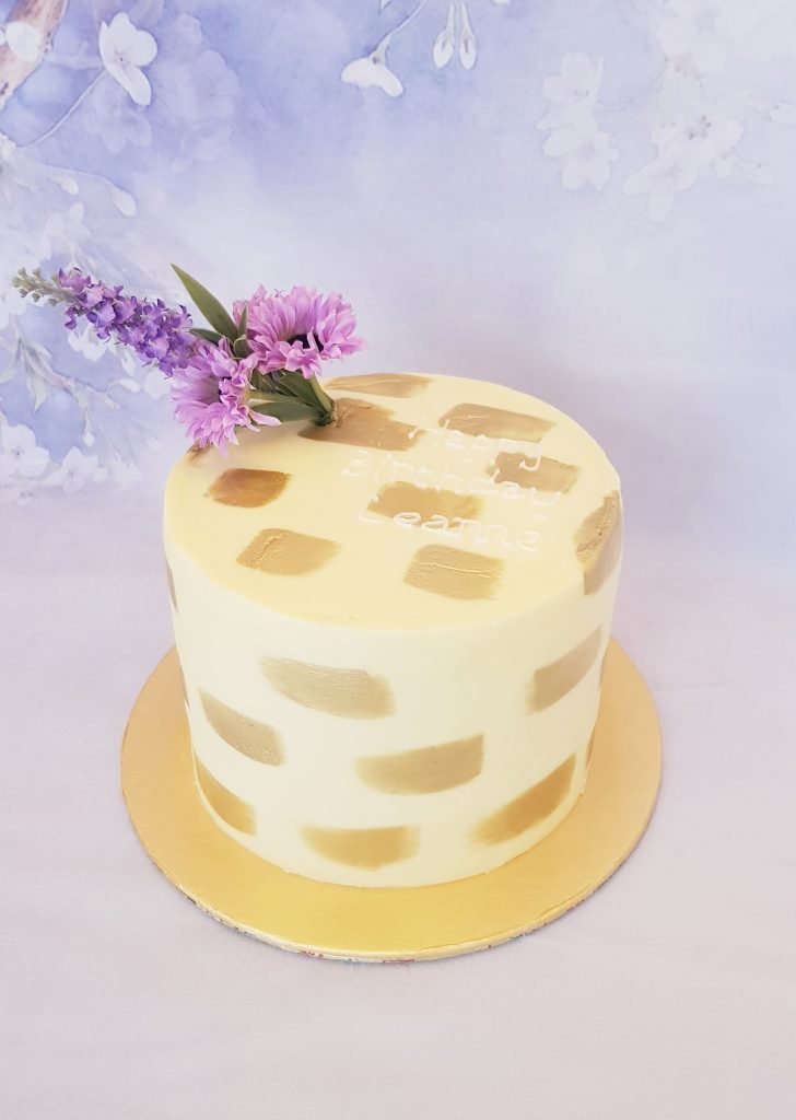 Ivory and gold birthday cake with purple flowers on top