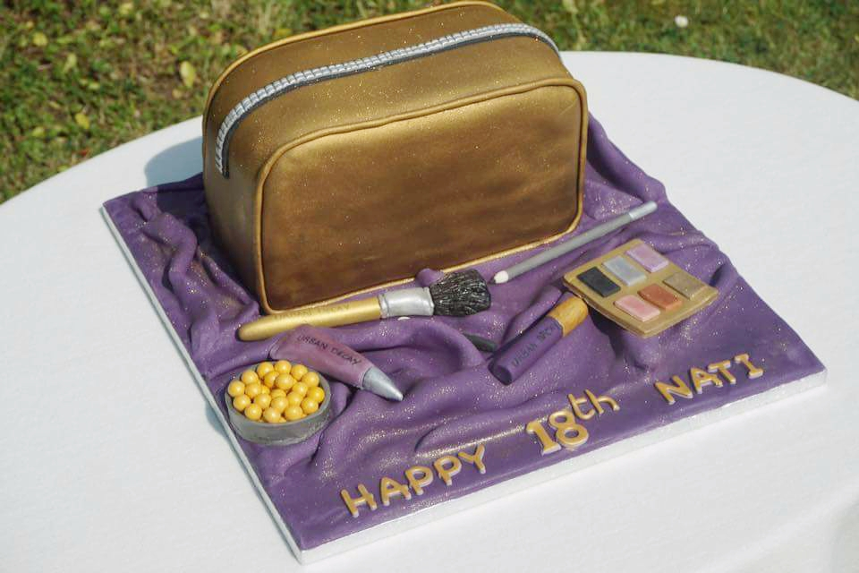 Make-up bag themed 18th birthday cake with make up items next to it