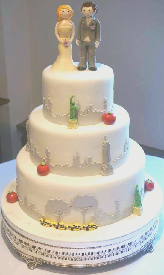 New york themed wedding cake with red apples and statue of liberty icons on the city skyline