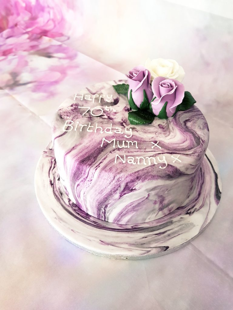 Purple marble effect 70th birthday cake with purple and white roses
