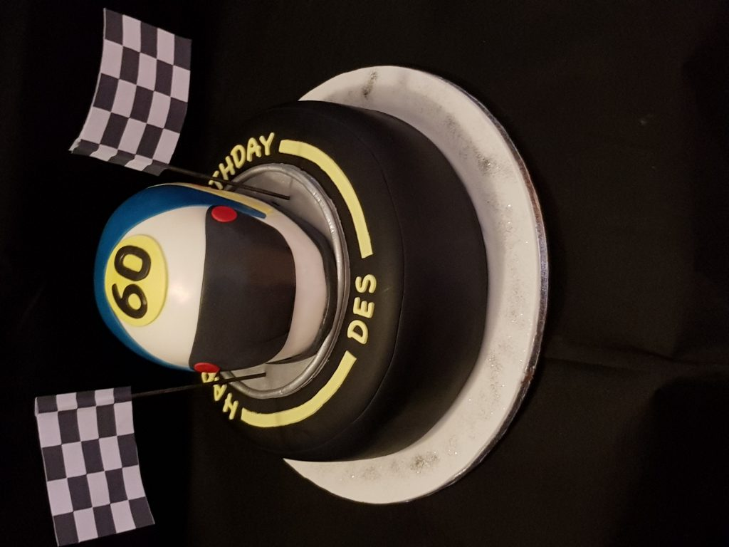 Racing theme 60th birthday cake with helmet and flag decorations