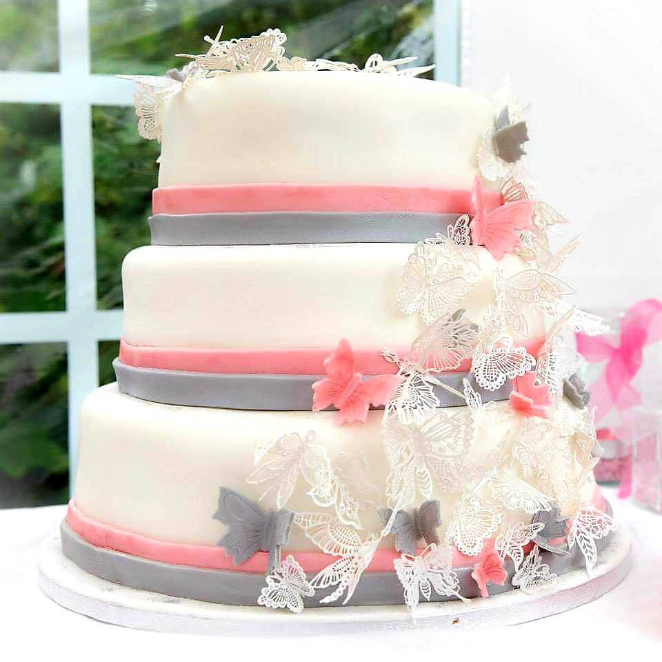 3 tier wedding cake with ivory icing and pink and grey butterfly decorations