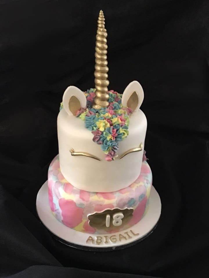 Multicoloured unicorn themed birthday cake with horn, ears and eyes