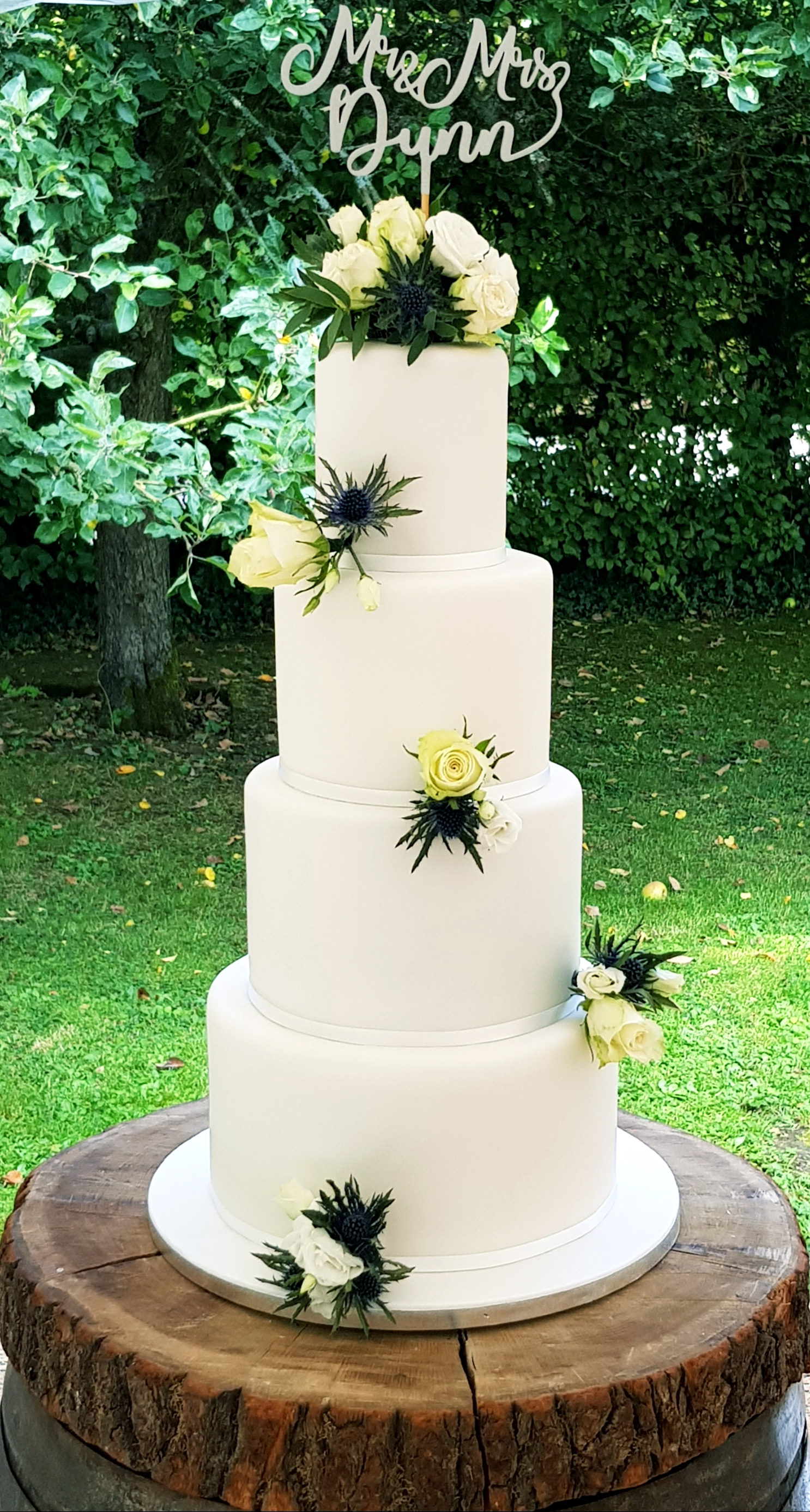 Classic 4 tier wedding cake with white icing and decorated with white roses and green foliage