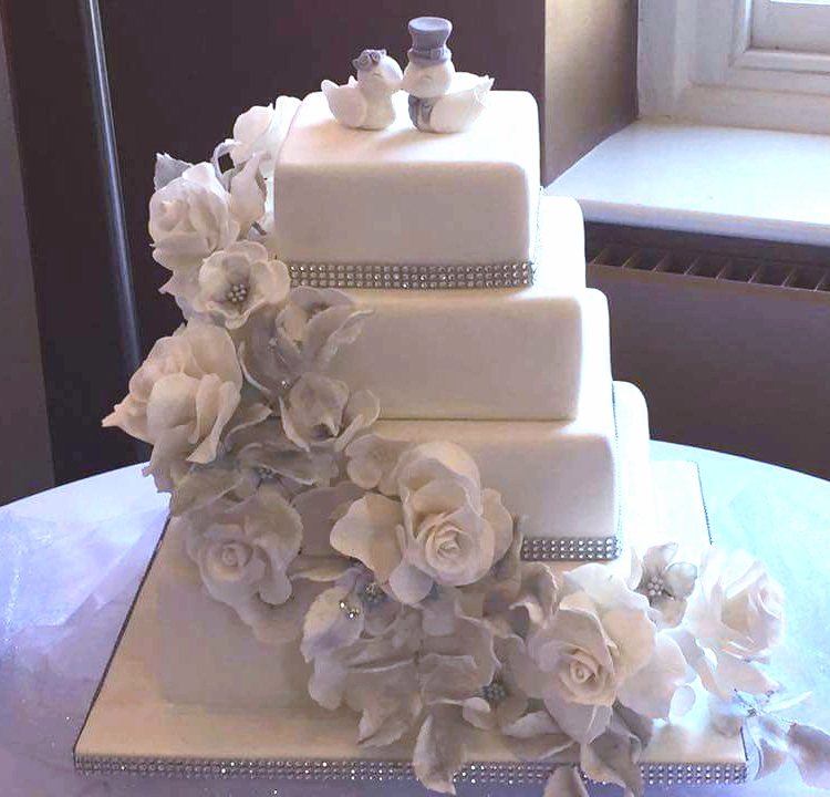 4 tier wedding cake with white icing and white and silver flower decorations