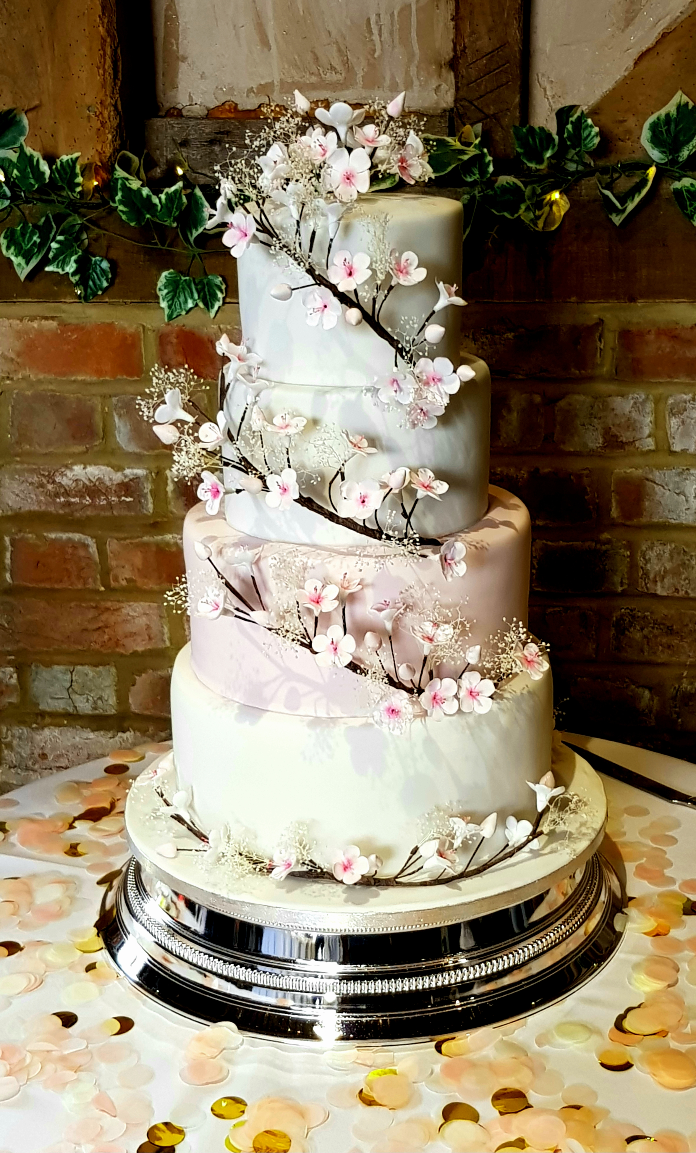 4 tier wedding cake decorated with white icing and wild orchids