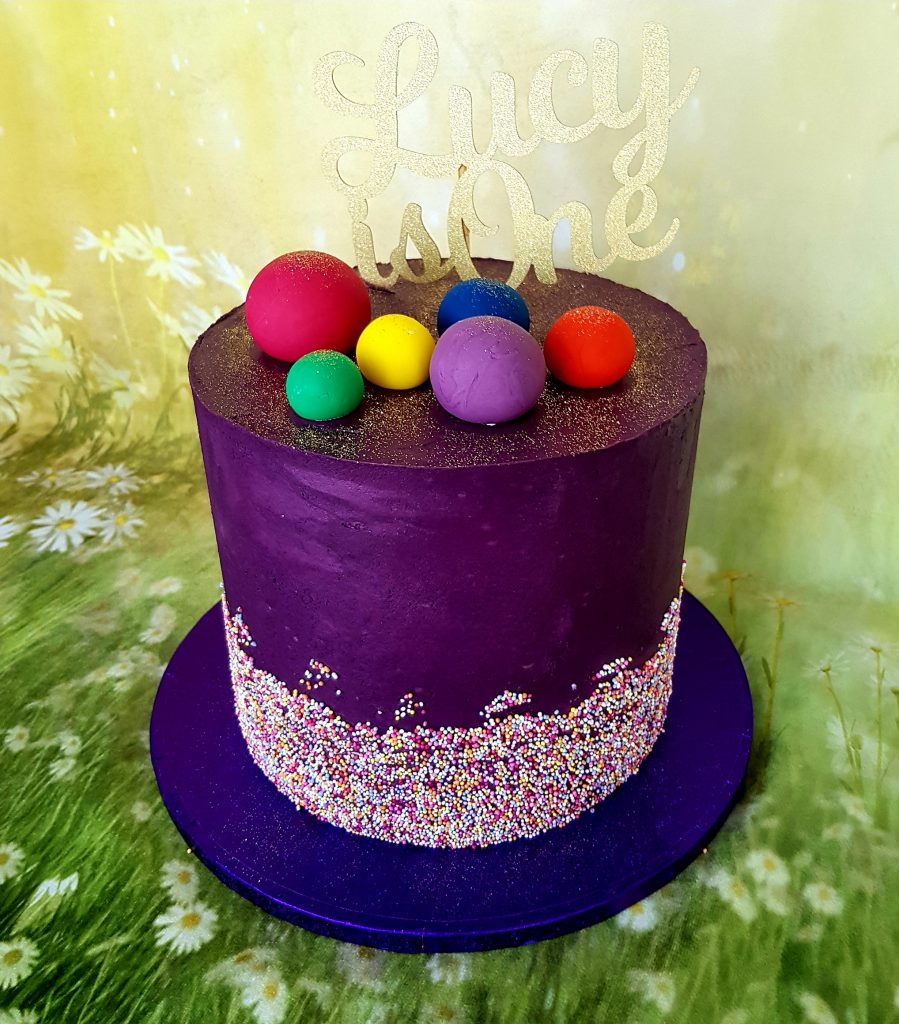 Purple tall cake with a band of hundreds and thousands and a Lucy is one cake topper.