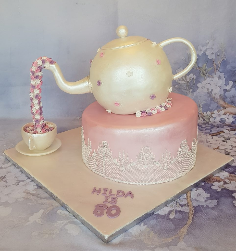 Teapot cake pouring flowers into tea cup