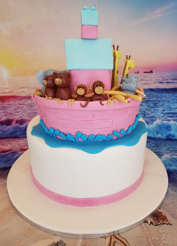 White, pink and blue cake topped with Noah's ark and animals